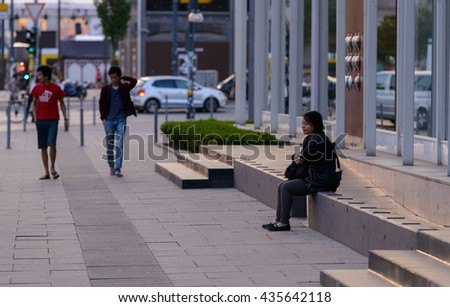 Berlin, Germany - May 11, 2016: An asian woman sitting alone by  the Berlin Congress Centre.