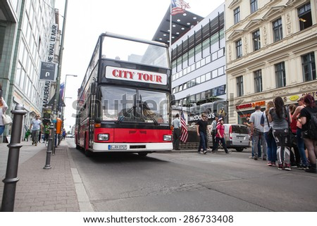 BERLIN, GERMANY - MAY 10, 2015: Bus at Checkpoint Charlie. The crossing point between East and west Berlin became a symbol of the Cold War. - stock photo