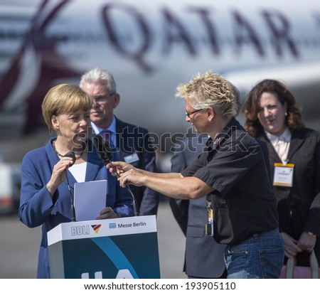 BERLIN, GERMANY - MAY 20, 2014: German Chancellor Angela Merkel (L) open up the International aviation and space exhibition ILA. In the Background, an Airbus A350.