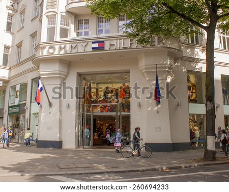 BERLIN, GERMANY - MAY 30, 2014: Pedestrians walk past a Tommy Hilfiger store. Tommy Hilfiger is an American fashion, apparel, design, fragrance retail company