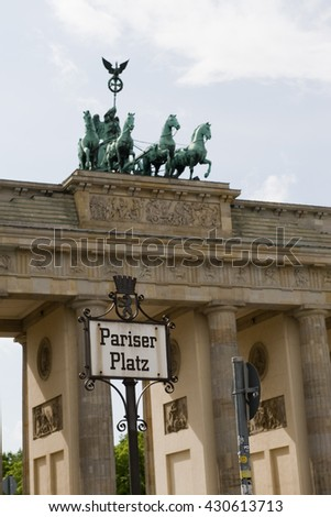 Berlin, Germany - May 15, 2016: View on quadriga on top of Brandenburg Gate and Pariser Platz sign in foreground.
