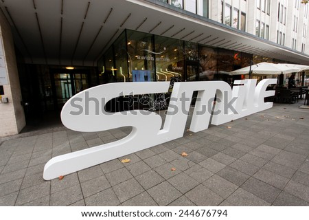 BERLIN, GERMANY - NOVEMBER 12, 2014: Dental care shop Swiss Smile with 3D logo on pavement at shopping street Kurfuerstendamm in Berlin, Germany on November 12, 2014.  - stock photo