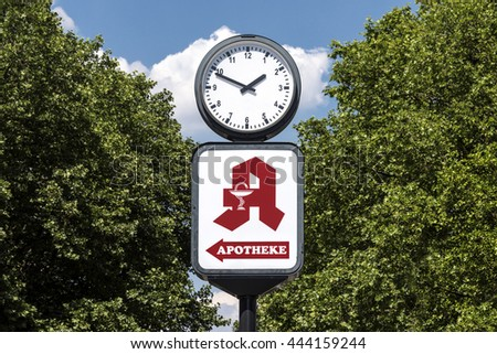 Berlin, Germany: Red pharmacy sign (Apotheke) and big clock with trees and blue sky in the background  - stock photo