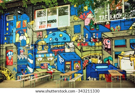 BERLIN, GERMANY - SEP 4: Colorful street art by unknown artist on wall of popular outdoor cafe on September 4, 2015. Urban area of Berlin comprised 4 million people, 7th most populous in EU