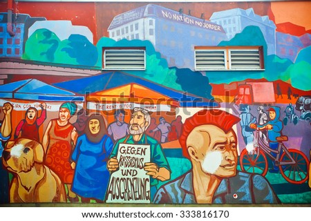 BERLIN, GERMANY - SEPT 1, 2015: Wall graffiti with crowd protesting against Illegal Immigration reform on Septemper 1, 2015. Urban area of Berlin comprised 4 million people, 7th most populous in EU - stock photo