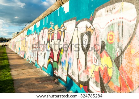 BERLIN, GERMANY - SEPTEMBER 28, 2015:  Graffiti at the East Side Gallery in Berlin, Germany. The East Side Gallery is the longest preserved stretch of the Berlin wall and was painted by artists in - stock photo