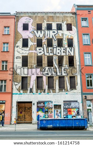 BERLIN, GERMANY - SEPTEMBER 13: Mural Wir bleiben alle on September 13, 2013 in Berlin. The message is painted on squated building in Brunnen street in Berlin. - stock photo