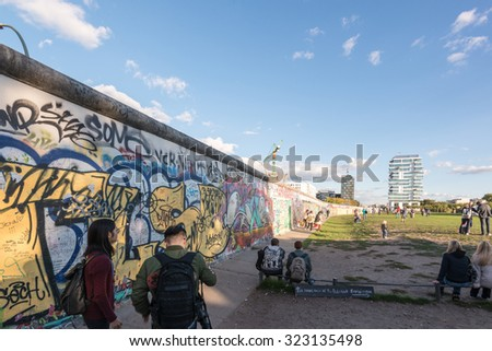 BERLIN, GERMANY - SEPTEMBER 28, 2015:  People enjoying the atmosphere at the East Side Gallery in Berlin, Germany. The East Side Gallery is the longest preserved stretch of the Berlin wall and was - stock photo