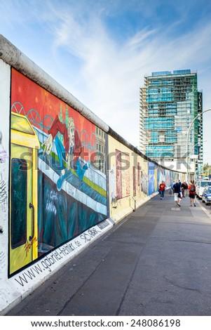 BERLIN - GERMANY - SEPTEMBER 29 :People walks along the Berlin Wall in East Side Gallery - over 1 km long part of historical Berlin Wall. ; September 29, 2014 in Berlin, Germany - stock photo