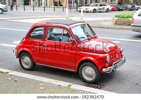 BERLIN, GERMANY - SEPTEMBER 12, 2013: Red Fiat 500 retro car at the city street. - stock photo