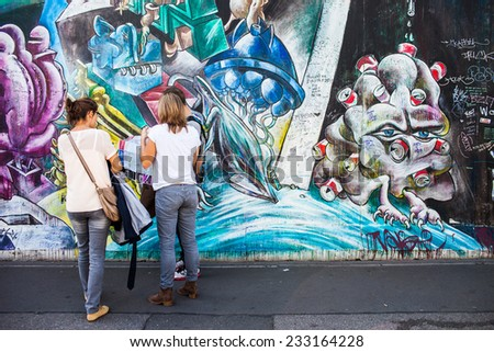 BERLIN - GERMANY - September 29, 2014. Tourists look at mural paintings at East Side Gallery - over 1 km long mural gallery. Berlin, Germany, September 29, 2014 - stock photo