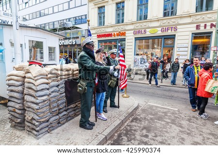 Berlin, Grmany - May 15, 2016: unidentified people at Checkpoint Charlie. Checkpoint Charlie was the best-known Berlin Wall crossing point between East Berlin and West Berlin, during the Cold War - stock photo