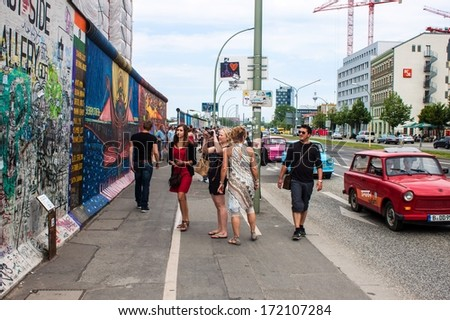 BERLIN - JUN 8: Tourists visit East Side Gallery on Jun 8, 2013 in Berlin, Germany. It is a 1,3 km long part of original Berlin wall, famous memorial with many grafittis. - stock photo