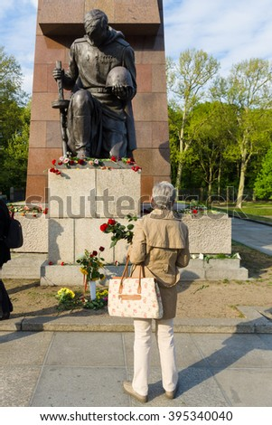 BERLIN - MAY 08, 2015: Victory in Europe Day. Treptower Park. A woman lays flowers at the statue of a kneeling soldier.
