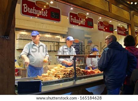 BERLIN - NOVEMBER 8: People buy sausages at traditional Christmas market on Potsdamer Platz on November 8, 2013 in Berlin, Germany - stock photo
