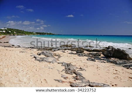 Bermuda beach during a hot summer day.  Photo includes the sky, rocky coastline, pink sand and the tide rolling in. - stock photo