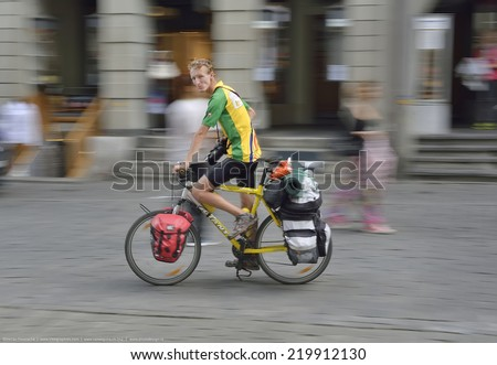 BERN, SWITZERLAND - AUGUST 16: Photo of a biker traveling around Switzerland on August 16, 2014. Cycling with panniers is a popular way of visiting countries.  - stock photo