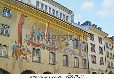 BERN, SWITZERLAND - MARCH 3, 2011: The old fresco on the building facade in Rathausgasse street depicts musicians and dancing couples in modest dresses, on March 3 in Bern.