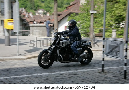 BERN, SWITZERLAND - 03 May 2009: Unknown man riding a motorcycle on the street with blur movement