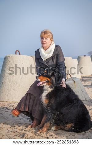 bernese mountain dog and woman sitting near sea - stock photo