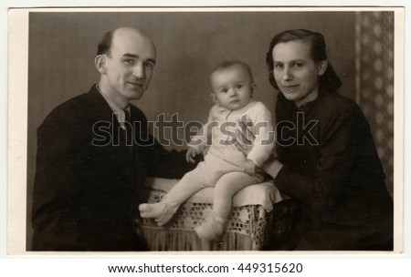 BEROUN, THE CZECHOSLOVAK REPUBLIC - MARCH 1, 1944: : Retro photo shows family with toddler. Vintage black & white photography.