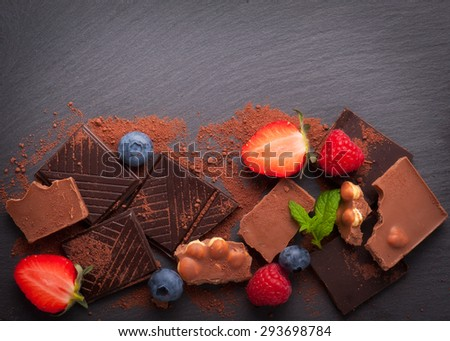 berries and chocolate on the black background - stock photo