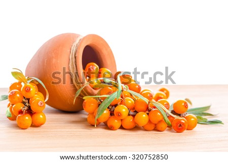 berries are scattered out of a ceramic pot on a wooden background - stock photo