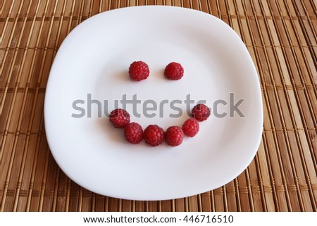 berries fresh raspberries laid out in the form of smiley joy background
