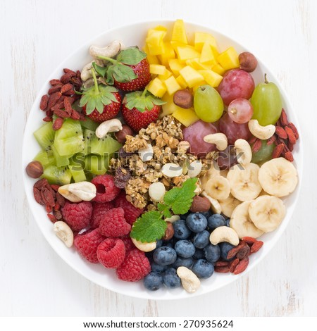 berries, fruits, nuts and granola, products for a delicious healthy breakfast, top view, close-up - stock photo