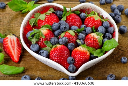 Berries in heart shaped bowl. Healthy diet eating concept.