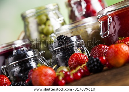 Berries jam in glass jar and wood background - stock photo
