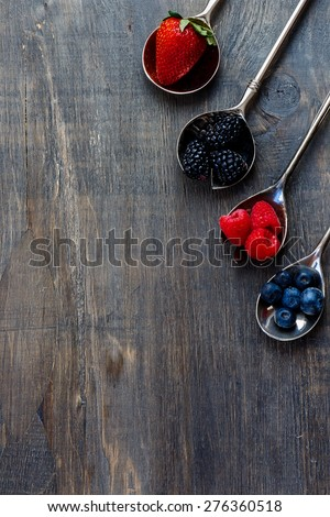 Berries mixed on vintage metal spoons over dark wooden board. Agriculture, Gardening, Harvest Concept. Background with space for text. - stock photo