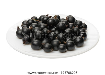 Berries of a black currant on a white plate on a white background, isolated  - stock photo