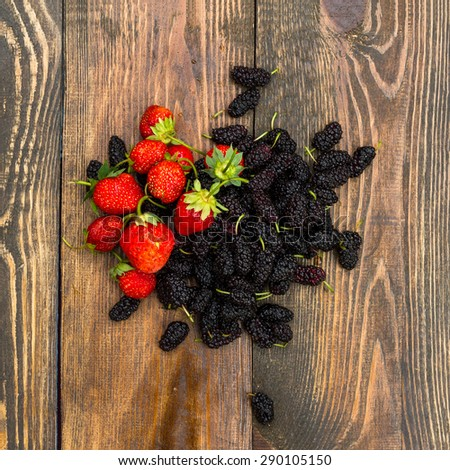 Berries of strawberry and mulberry on wooden table - stock photo