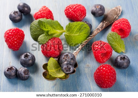 Berries on Blue Wooden Background. Summer or Spring Organic Berry over Wood. Raspberries, Blueberry, Vintage Spoon and Mint. Agriculture, Gardening, Harvest Concept - stock photo
