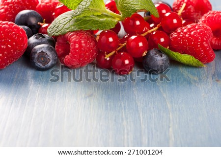 Berries on Blue Wooden Background. Summer or Spring Organic Berry over Wood. Raspberries, Blueberry, Red Currant and Mint. Agriculture, Gardening, Harvest Concept. Copy space. - stock photo