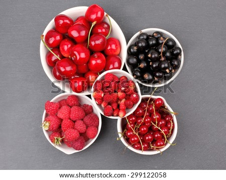 Berries on Stone Background. Summer or Spring Organic Berry over Stone. currant, red currant, Raspberries, Strawberry and Cherry. Agriculture, Gardening, Harvest Concept - stock photo