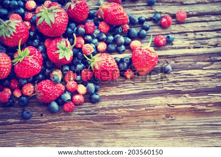 Berries on Wooden Background. Summer or Spring Organic Berry over Wood. Agriculture, Gardening, Harvest Concept - stock photo