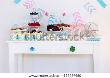 Berries, popcorn, canapes, candies, chocolate cake pops and a cake on a dessert table at party - stock photo