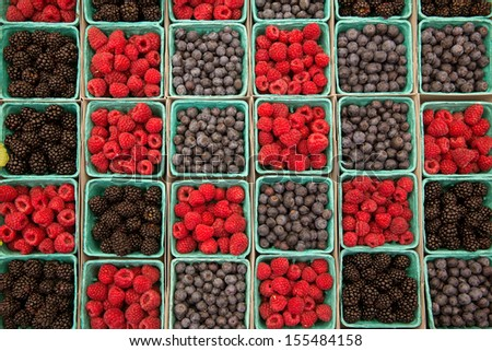 Berries raspberries blueberries and blackberries in a row on green boxes at market - stock photo