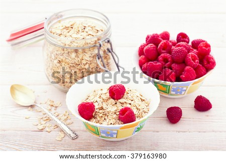 Berries raspberry, strawberry, currant and oatmeal. Summer breakfast. Ingredients for healthy breakfast - berries, fruit and muesli on white wooden table, close-up selective focus.