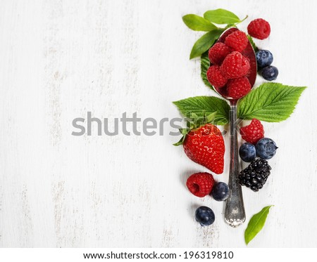 Berries with spoon  on Wooden Background. Strawberries, Raspberries and  Blueberries.  Health, Diet, Gardening, Harvest Concept  - stock photo