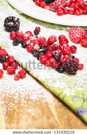 Berries with strawberry and redcurrants, dusted with powdered sugar. Shallow DoF - stock photo