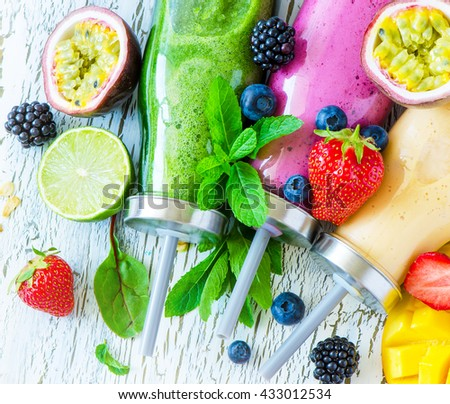 Berry and fruit smoothie in bottles, healthy summer detox yogurt drink, diet or vegan food concept, fresh vitamins, mango, lime - stock photo