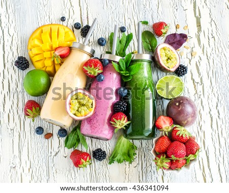 Berry and fruit smoothie in bottles, healthy summer detox yogurt drink, diet or vegan food concept, fresh vitamins, homemade refreshing cocktail - stock photo