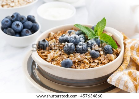 berry crumble with oatmeal in a ceramic form on white table, closeup, horizontal - stock photo
