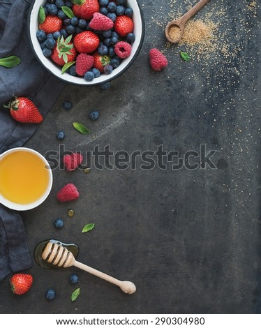 Berry frame with copy space on right. Strawberries, raspberries, blueberries and mint leaves, honey, cane sugar, dark grunge background, top view, copy space - stock photo