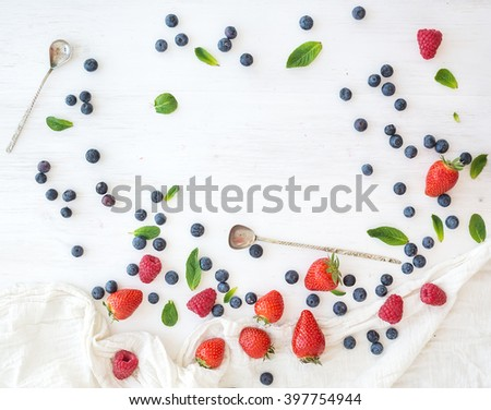 Berry frame with copy space on right. Strawberries, raspberries, blueberries and mint leaves, white wooden background, top view