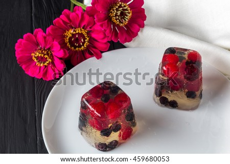 Berry jelly on plate and flowers. Closeup