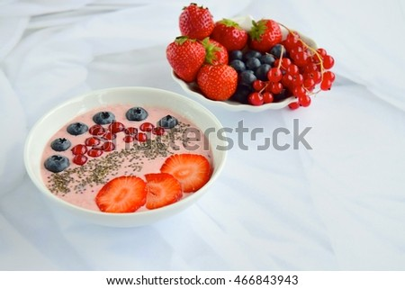 Berry smoothie bowl topped with strawberry, blueberry, red currant and chia seeds